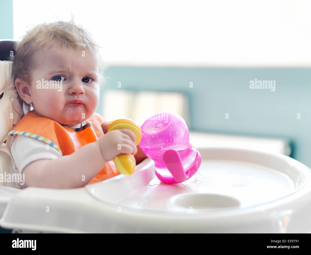 Baby girl playing with sippy cup in high chair - Stock Image