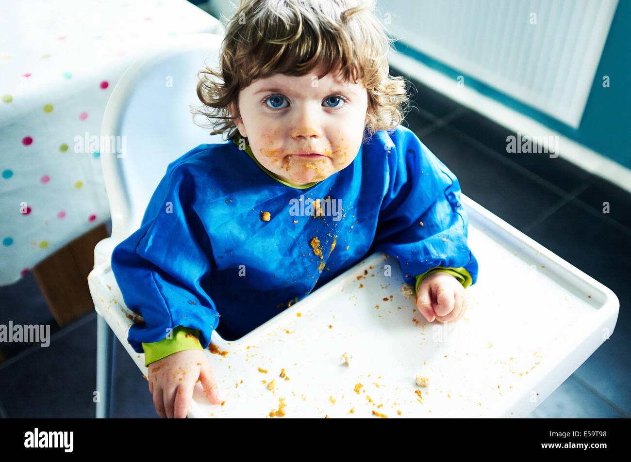Messy baby girl eating in high chair - Stock Image