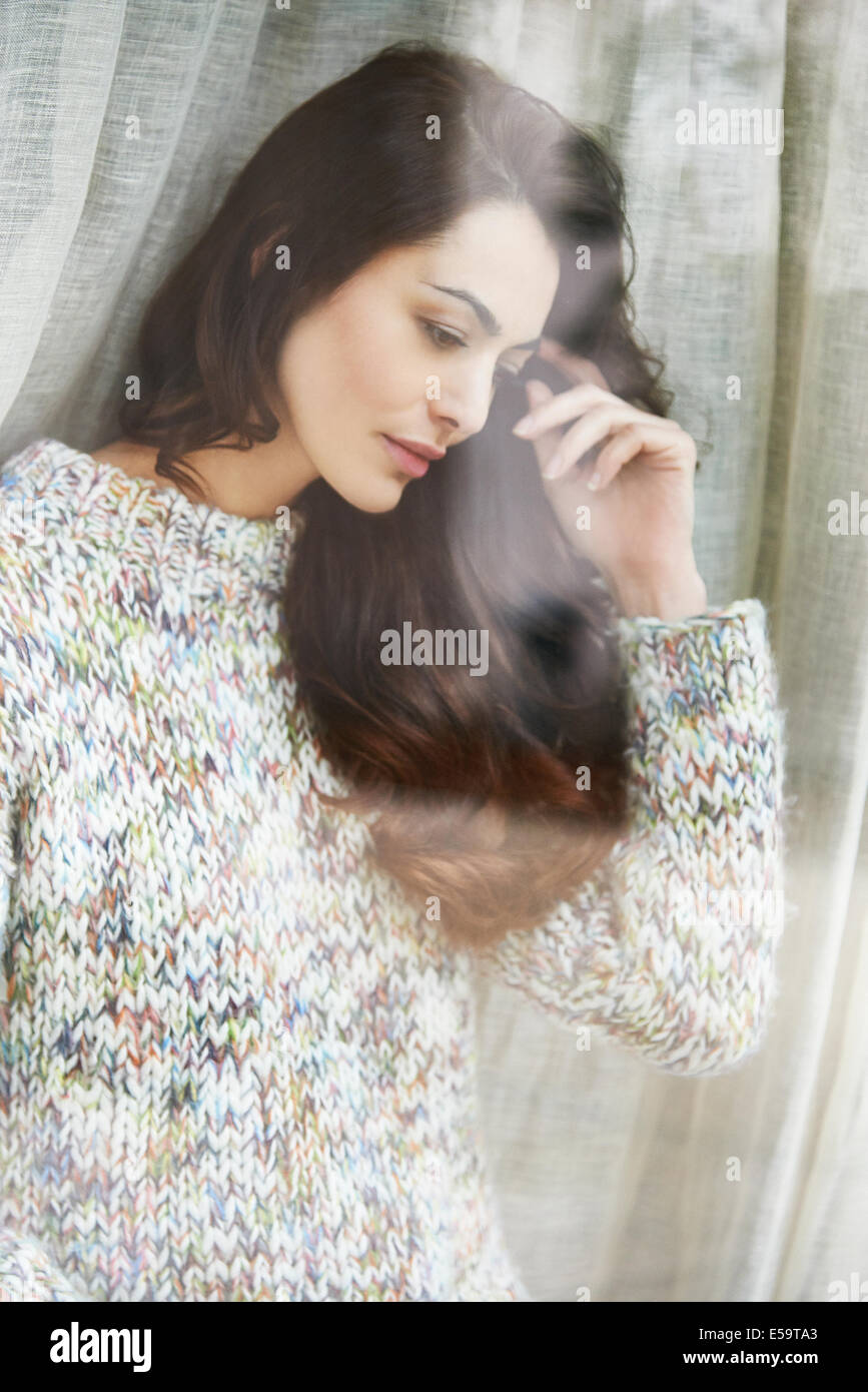 Woman standing by window - Stock Image
