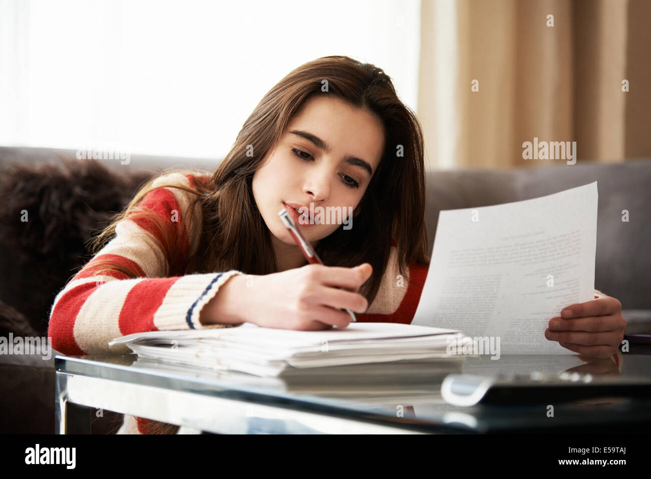 Girl doing homework at coffee table - Stock Image