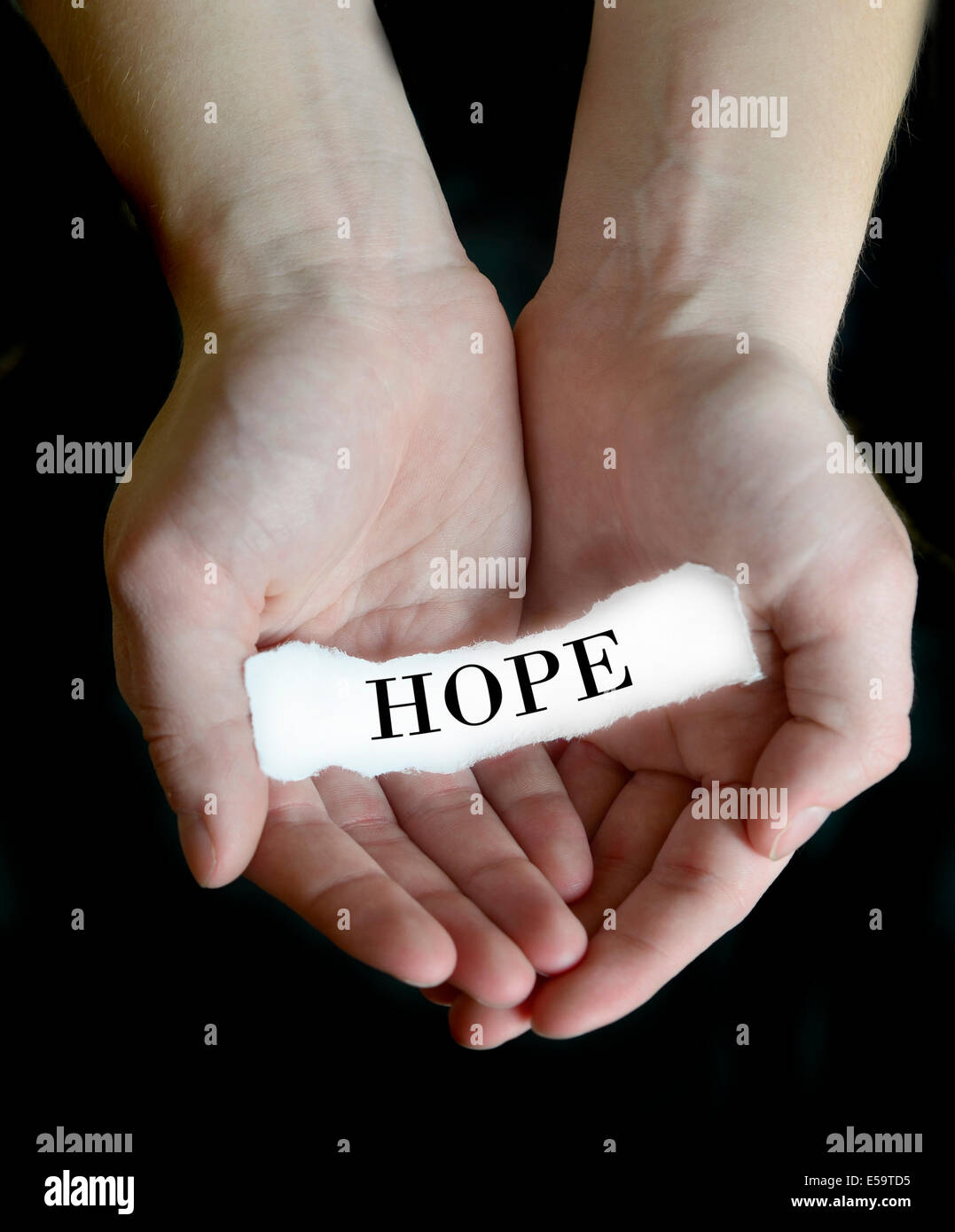 Person hands holding cupping paper message for Hope - Stock Image