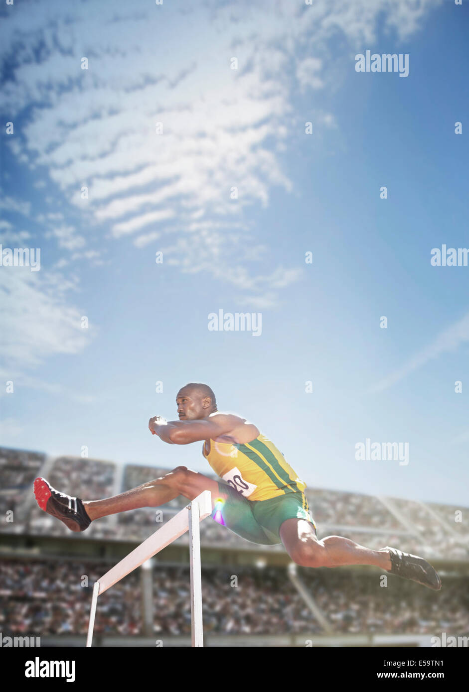 Track and field athlete jumping hurdle - Stock Image
