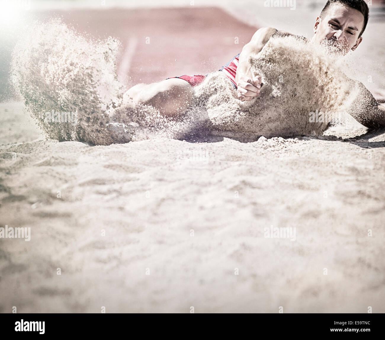 Long jumper landing in sand - Stock Image
