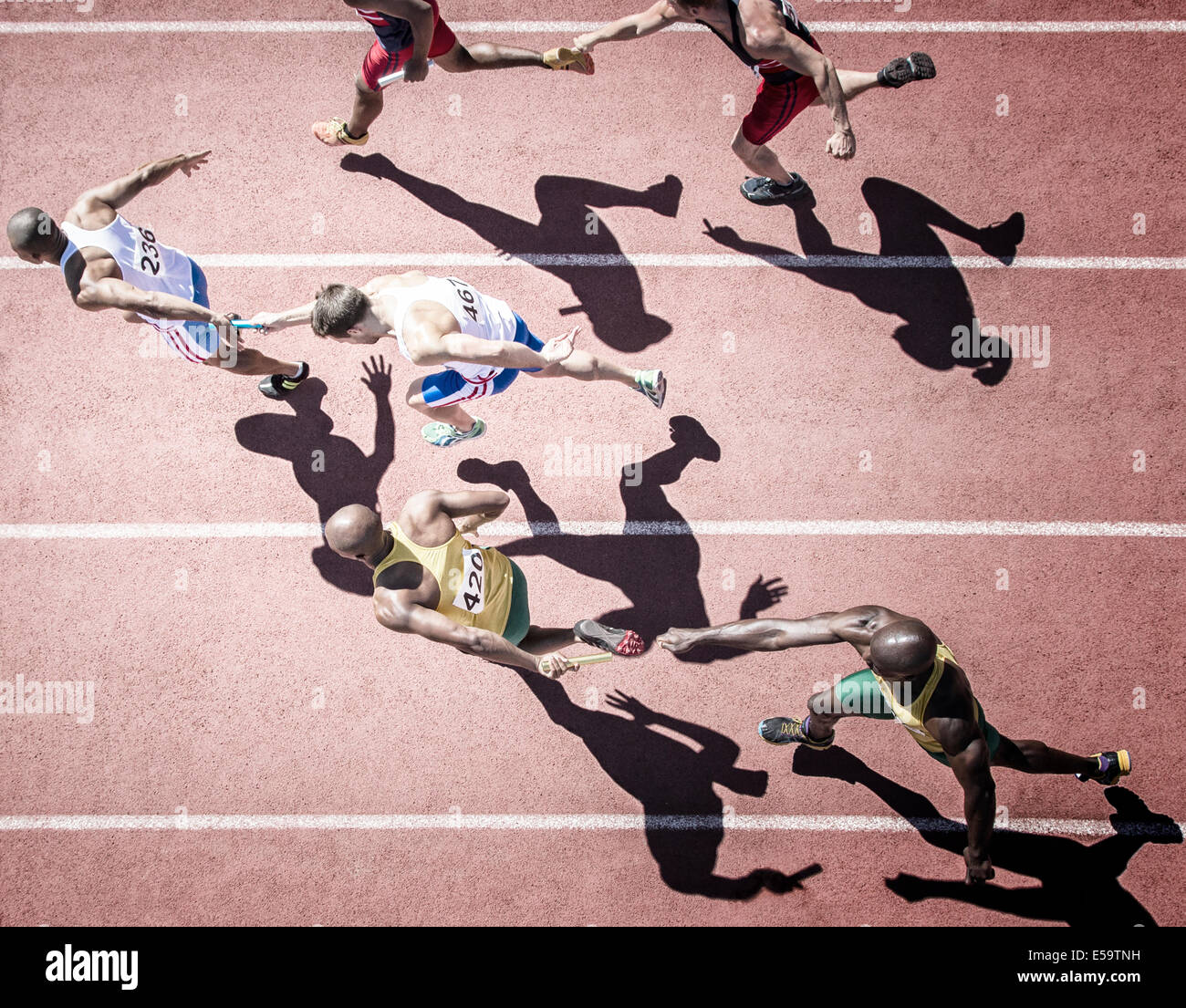 Relay runners handing off batons on track - Stock Image