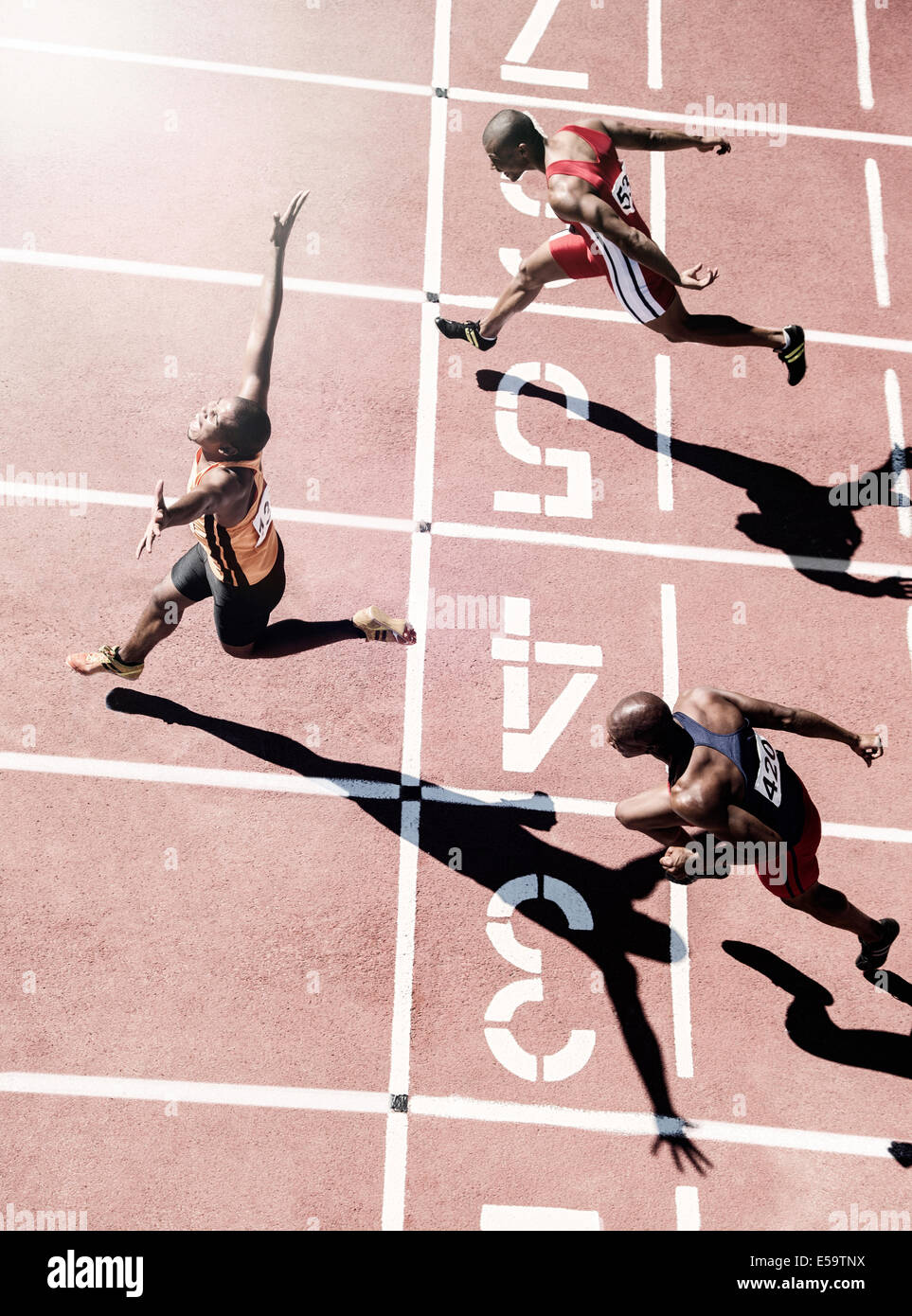 Runners crossing finish line - Stock Image