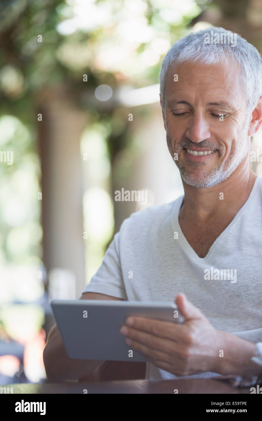 Man using digital tablet at table - Stock Image