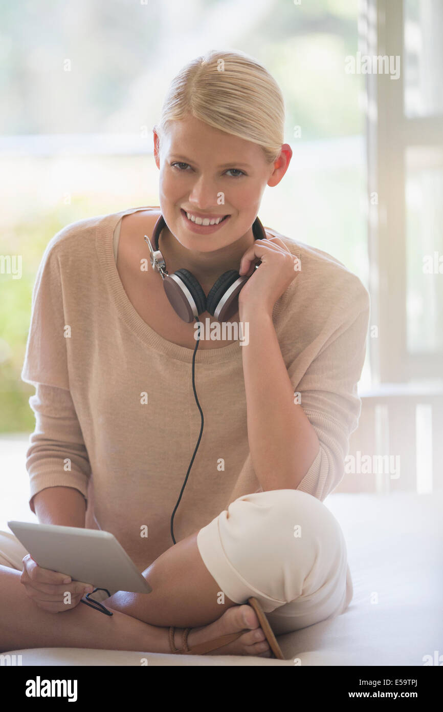 Woman using digital tablet with headphones - Stock Image