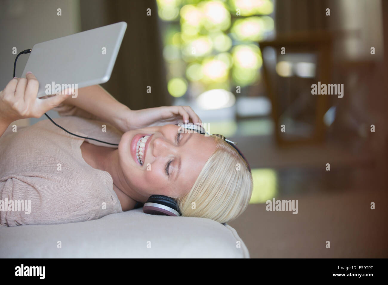 Woman using digital tablet and headphones - Stock Image