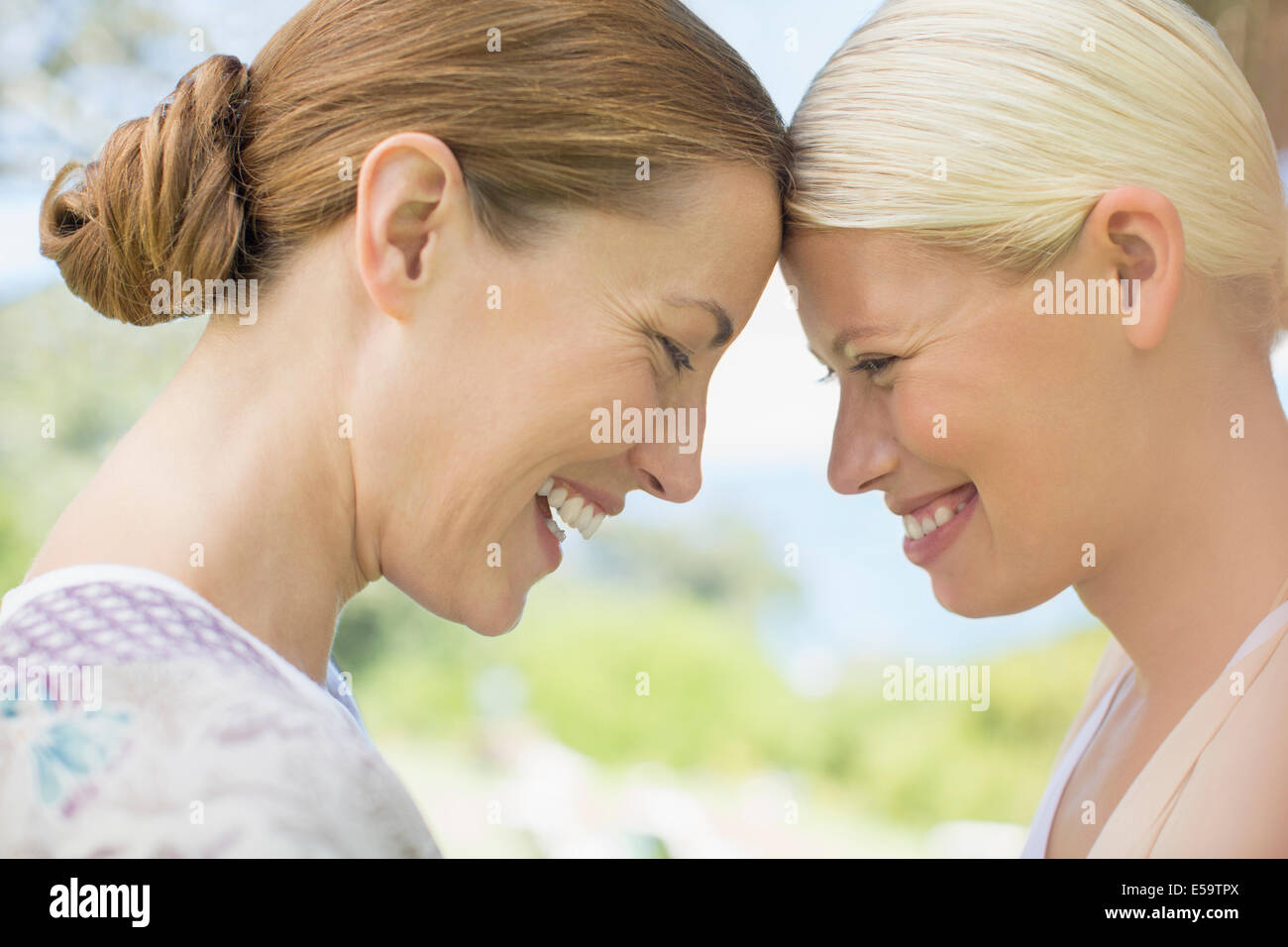 Women laughing together indoors - Stock Image