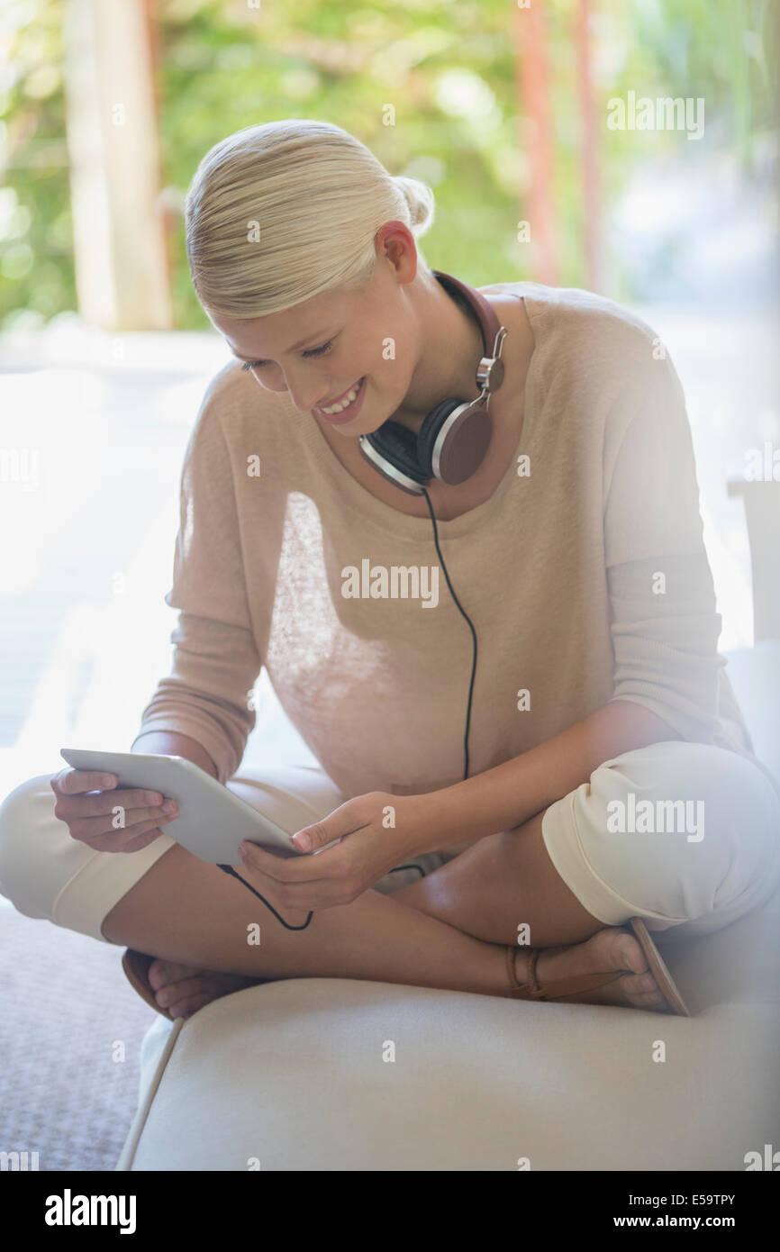 Woman using digital tablet on sofa - Stock Image