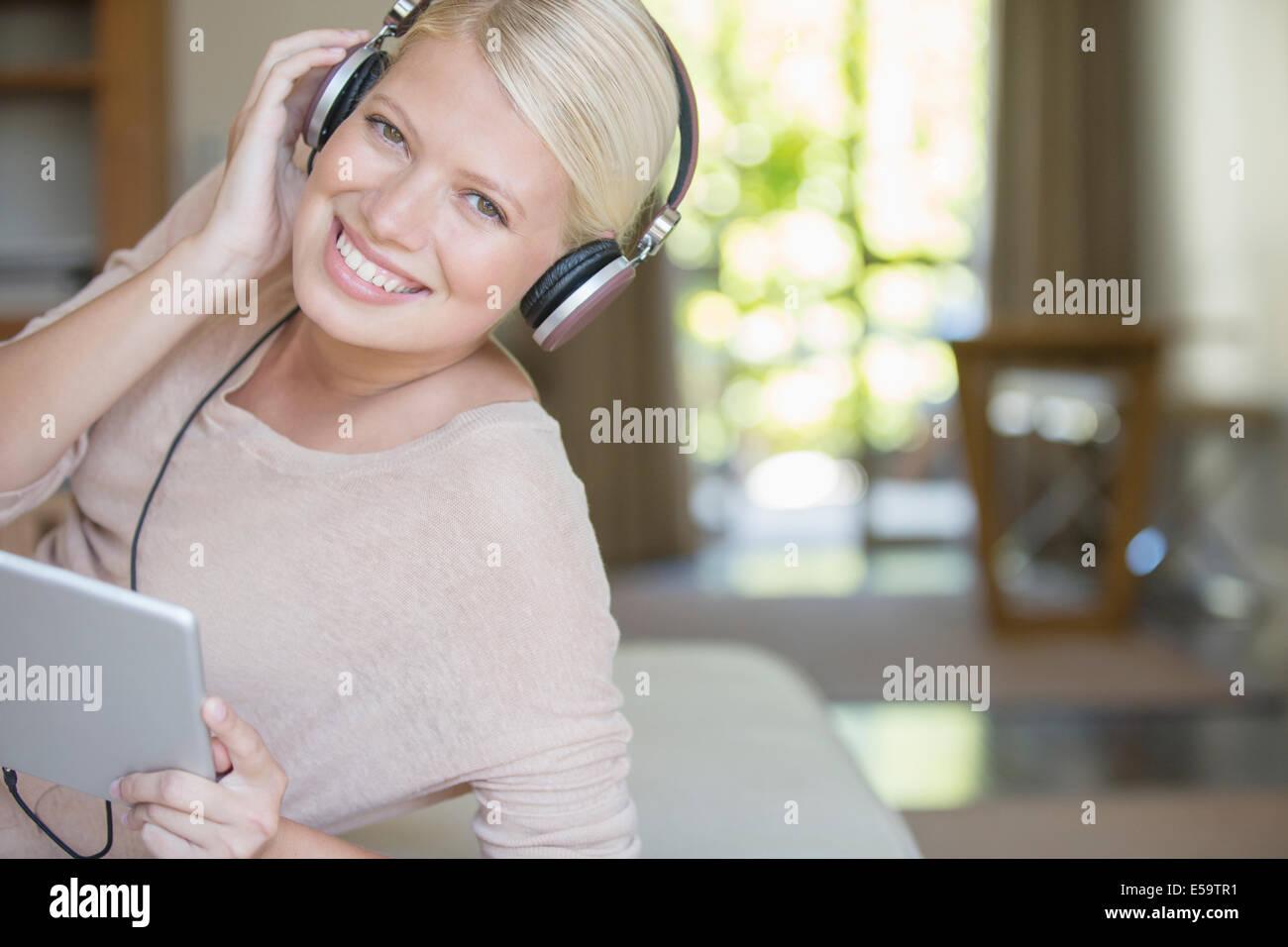 Woman using digital tablet and headphones - Stock Image