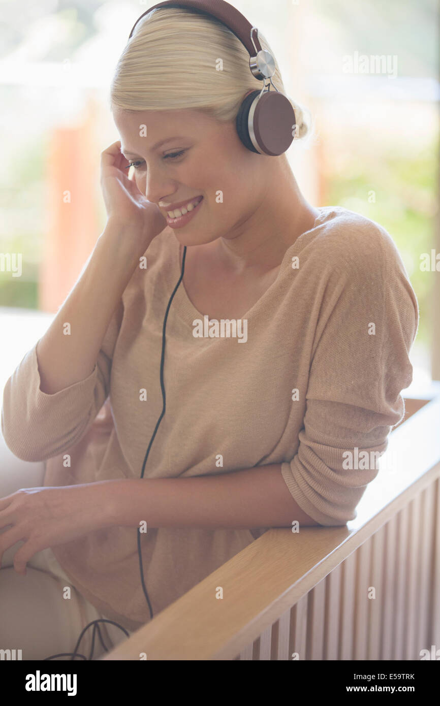 Woman listening to headphones on sofa - Stock Image