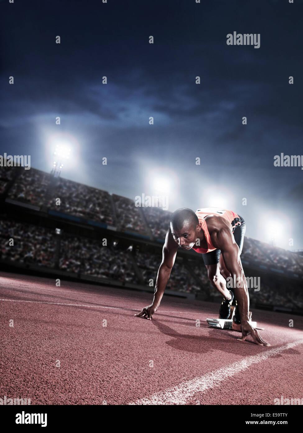 Runner poised at starting line on track - Stock Image
