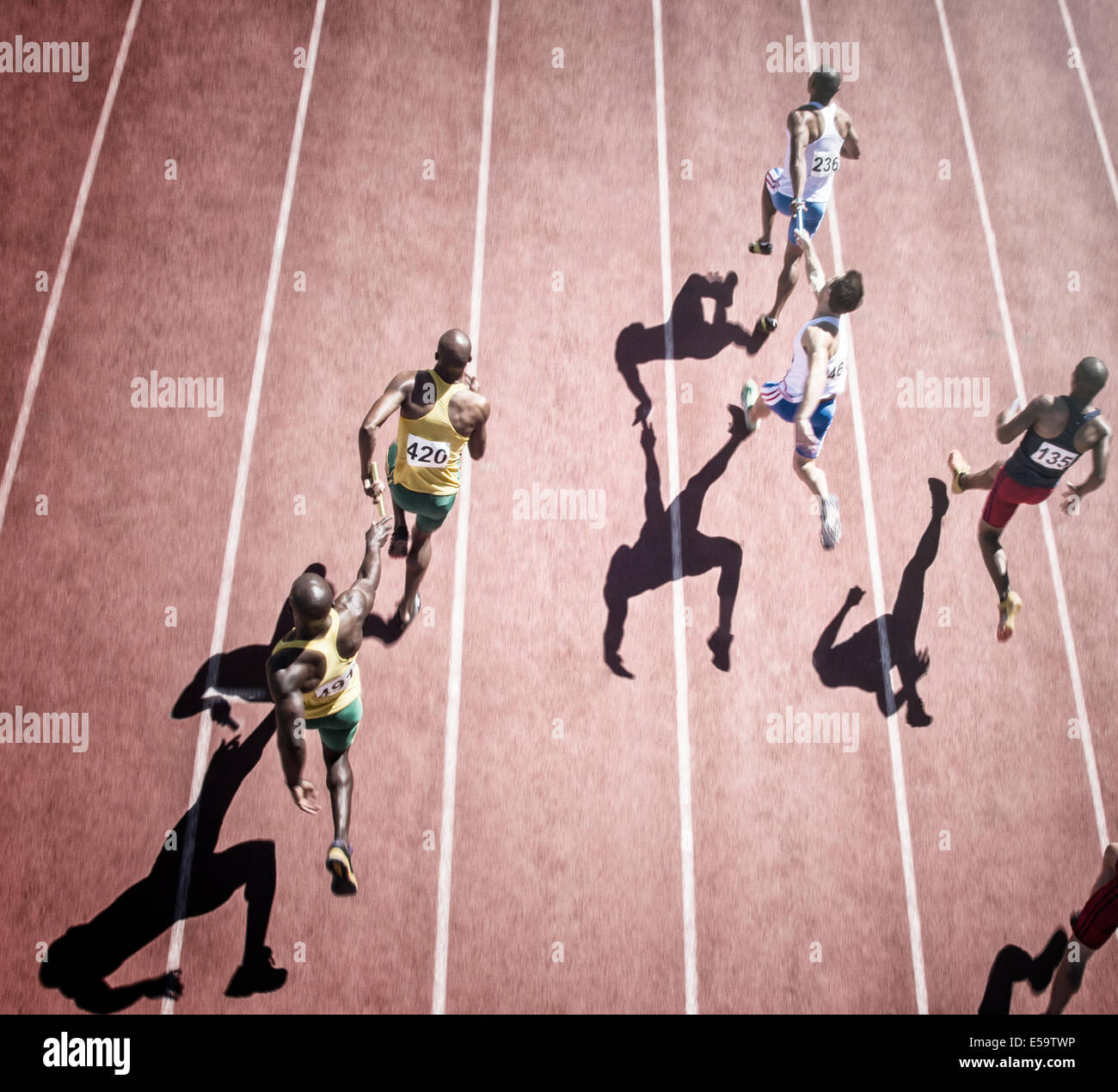 Relay runners handing off baton on track - Stock Image