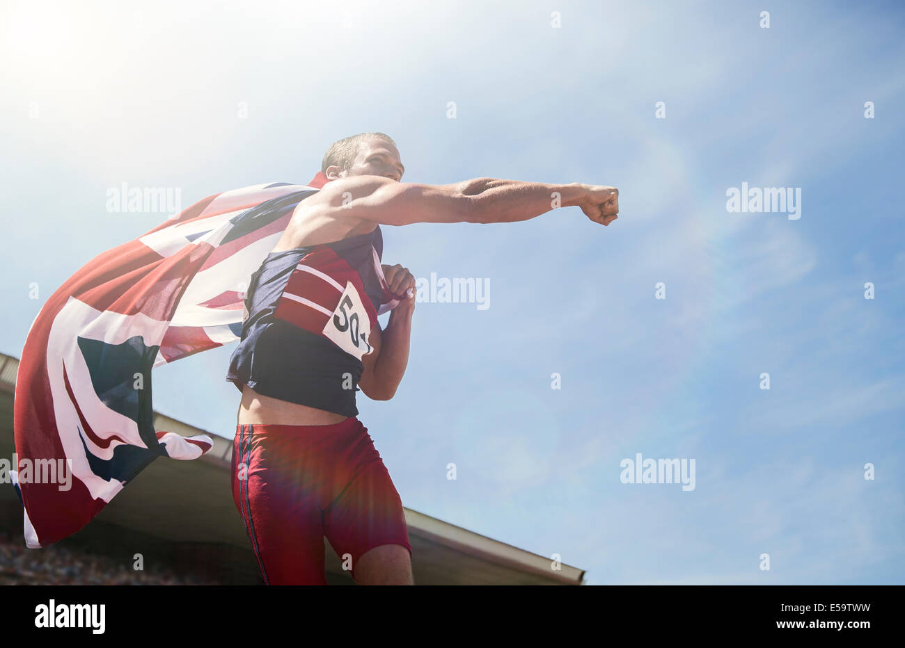 Track and field athlete cheering with British flag Stock Photo