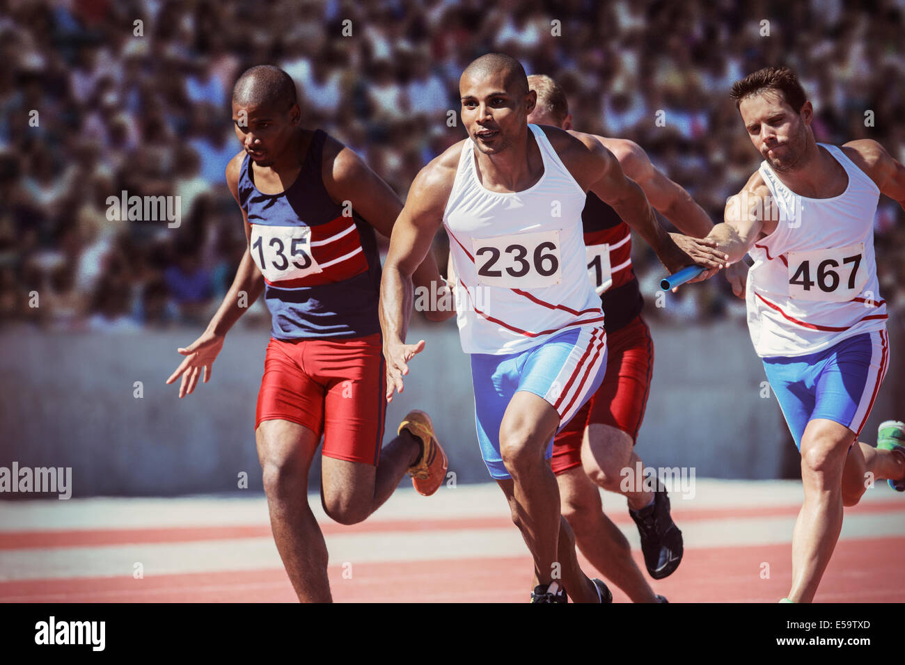 Relay runners exchanging batons on track - Stock Image