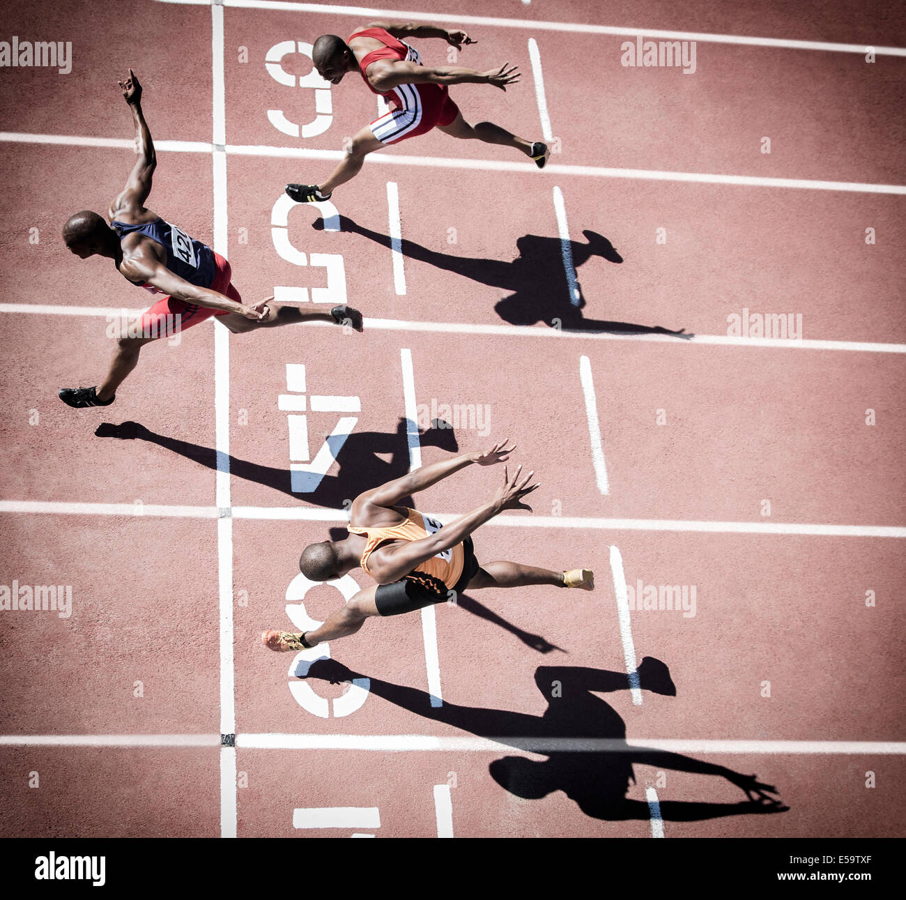 Runners crossing finish line on track - Stock Image