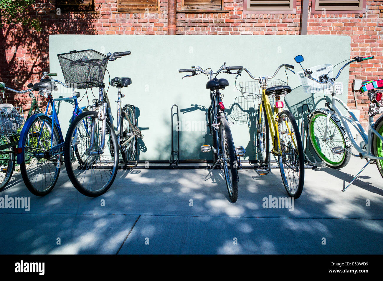 Bicycles lined up in rack on clear summer day - Stock Image