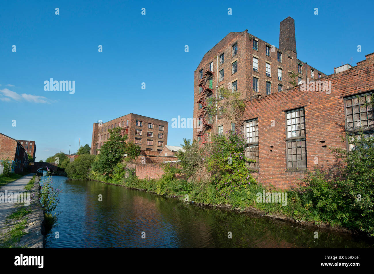 Two old warehouses by the side of the Ashton canal in Ancoats, Manchester, UK. - Stock Image