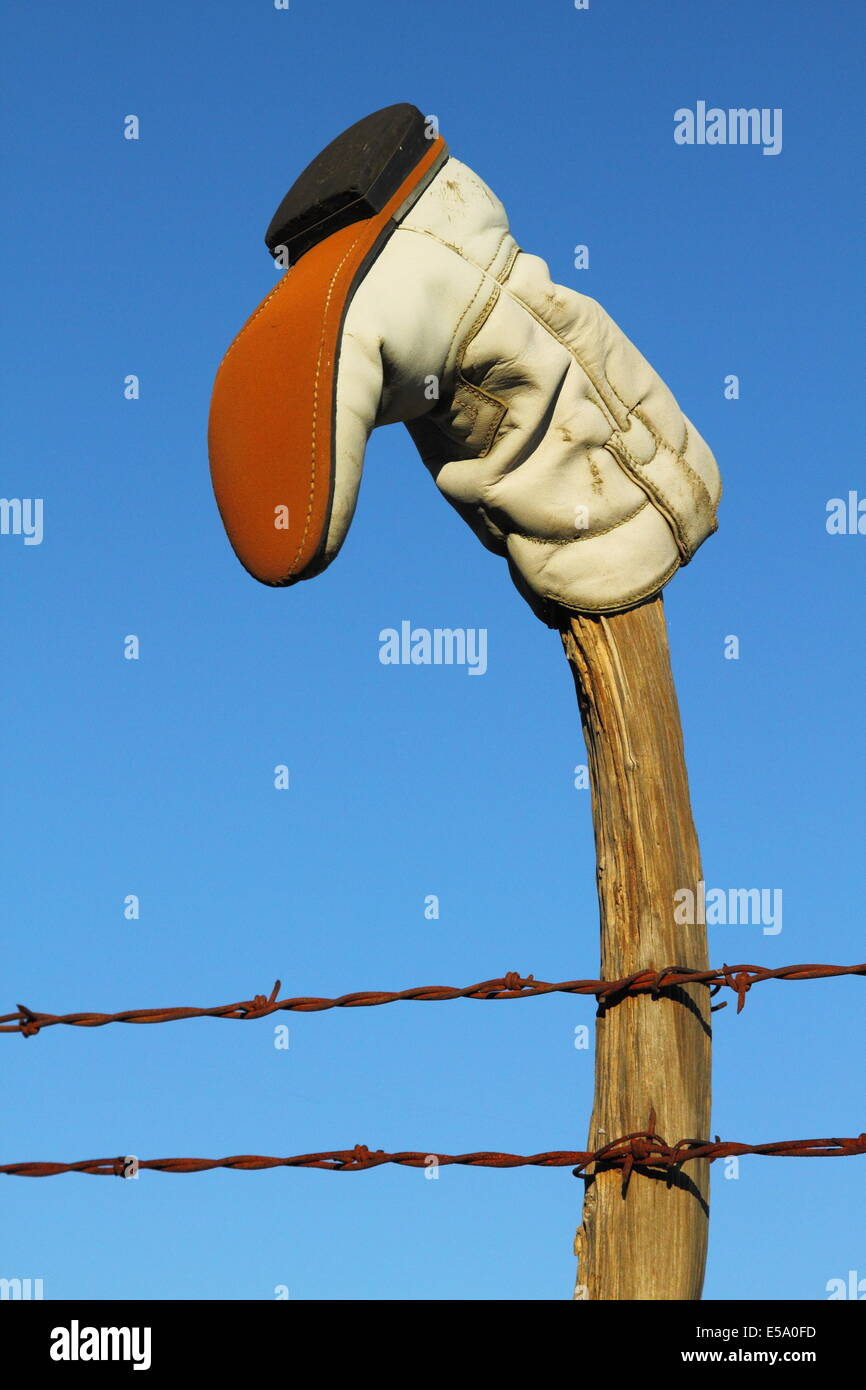 An old retired boot atop a wooden fence post. - Stock Image