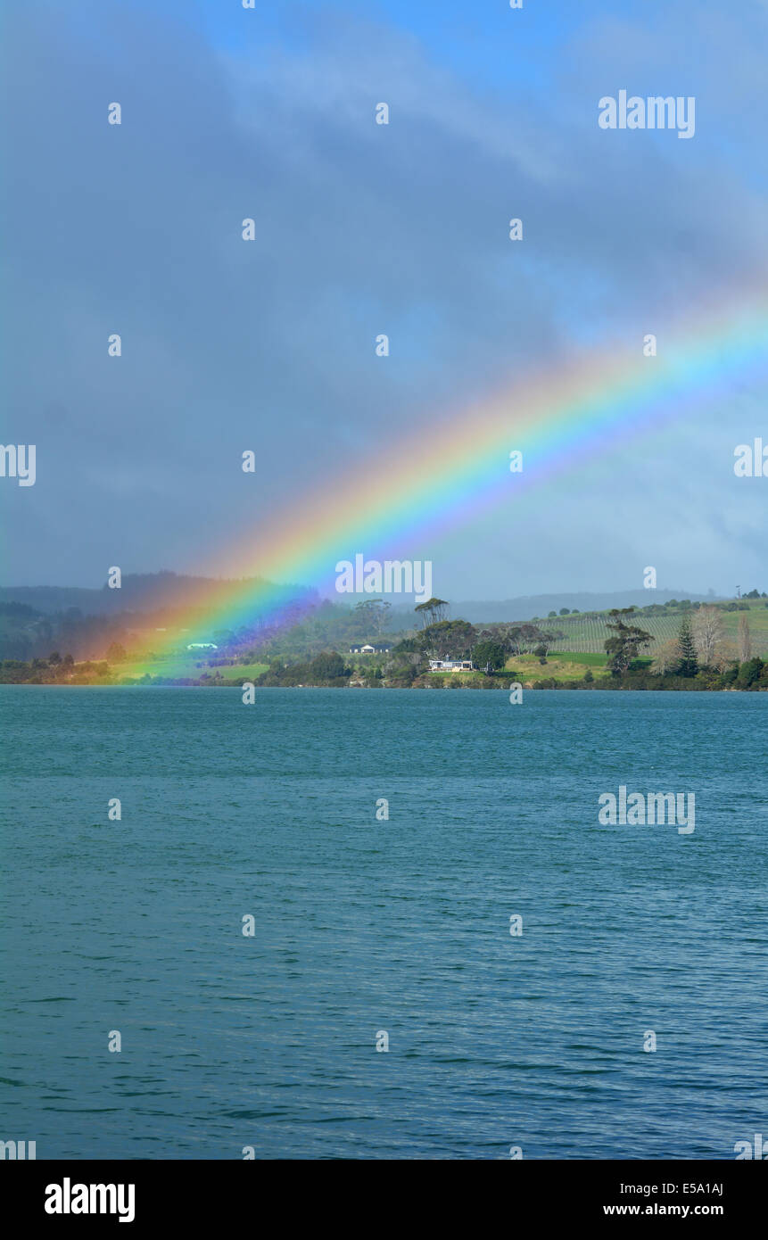 Rainbow in the sky and above the sea and rolling green countryside hills. - Stock Image