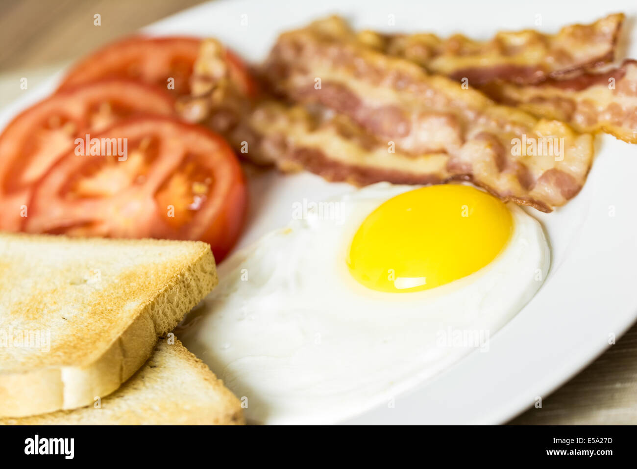 Tasty English Breakfast With Fried Egg, Bacon, Toast And Tomatoes Close Up Stock Photo