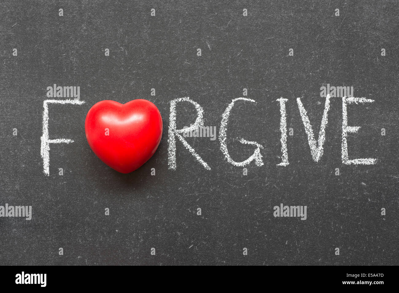 forgive word handwritten on chalkboard with heart symbol instead of O - Stock Image