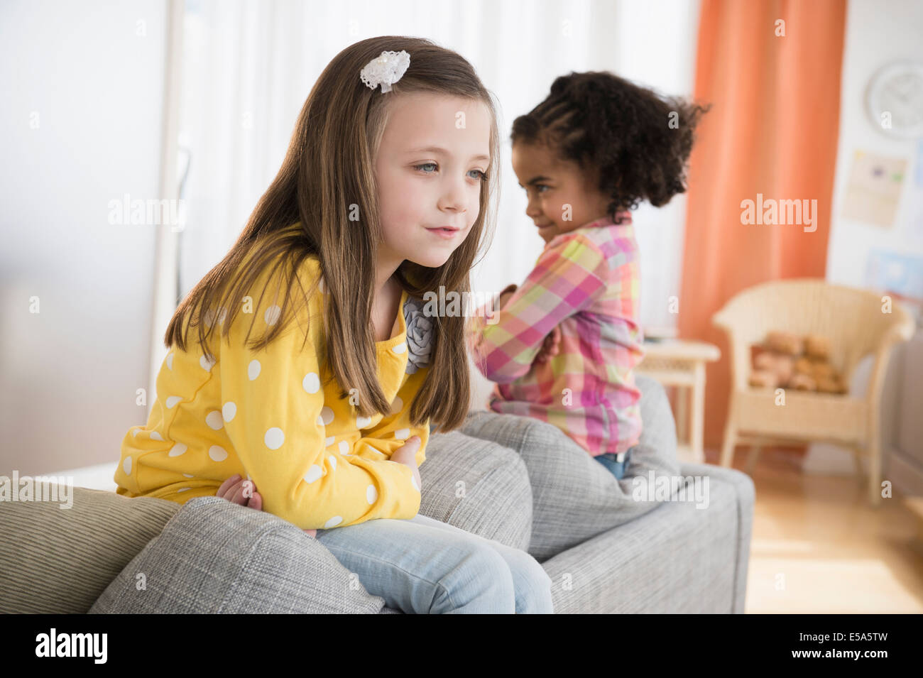 Girls fighting on sofa Stock Photo