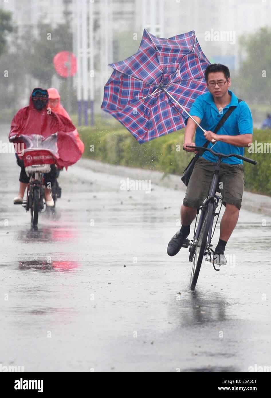 Yangzhou, China's Jiangsu Province. 25th July, 2014. Citizens ride against strong wind in Yangzhou, east China's Stock Photo