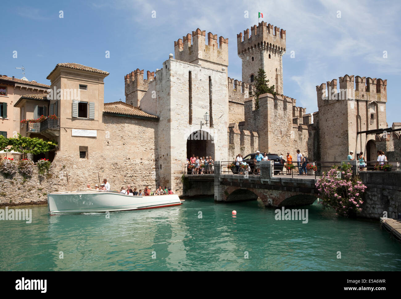 Tourists cross the bridge into the Scaliger Castle (or Rocca Scaligera) in Sirmione, Lake Garda, Italy - Stock Image