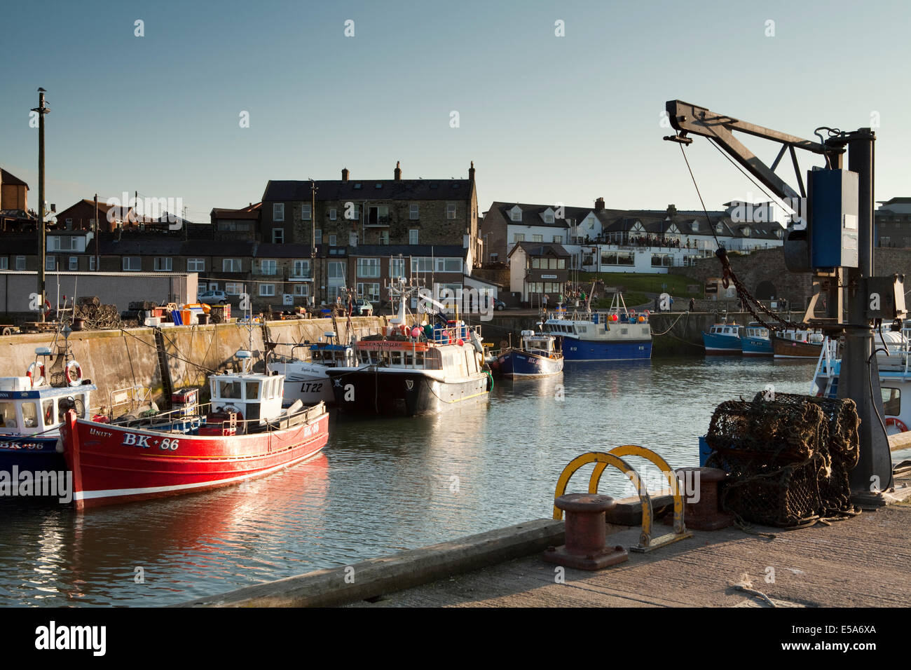 Seahouses Harbour in Northumberland - home to a small fishing fleet and many boats taking trips to the nearby Farne - Stock Image
