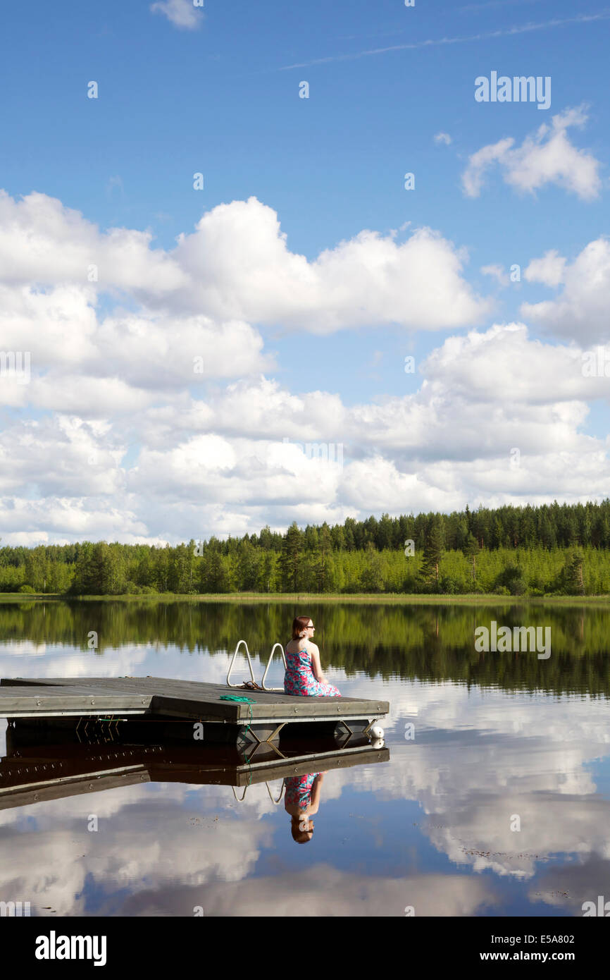 Lake scenery in summer in Finland with a woman sitting on pier - Stock Image