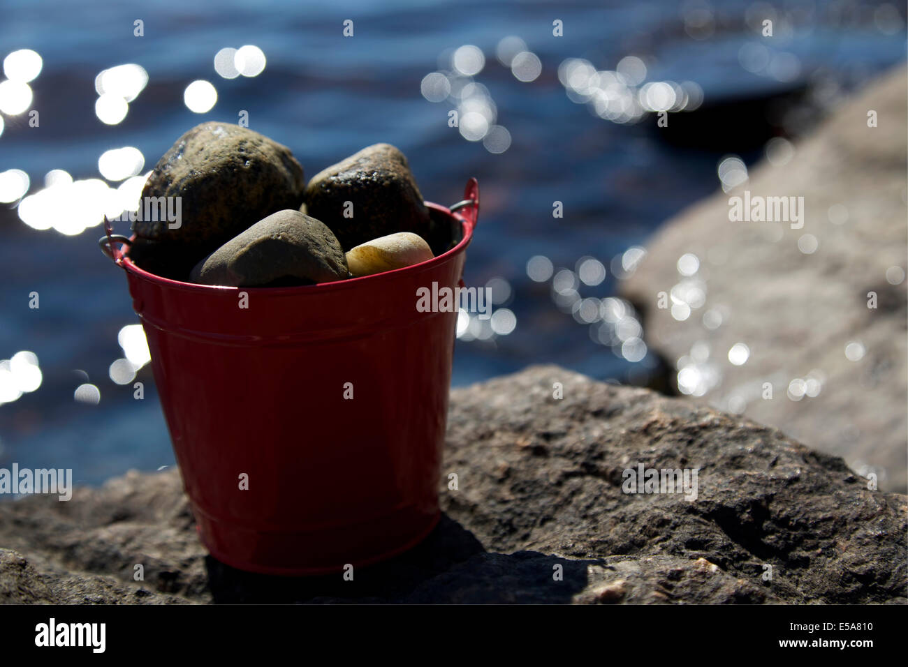 Red tin bucket full of rocks on top of a lakeside rock - Stock Image