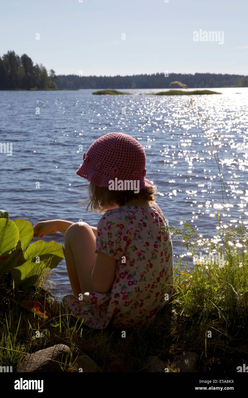 Girl sitting at lakeside in summer in Finland - Stock Image