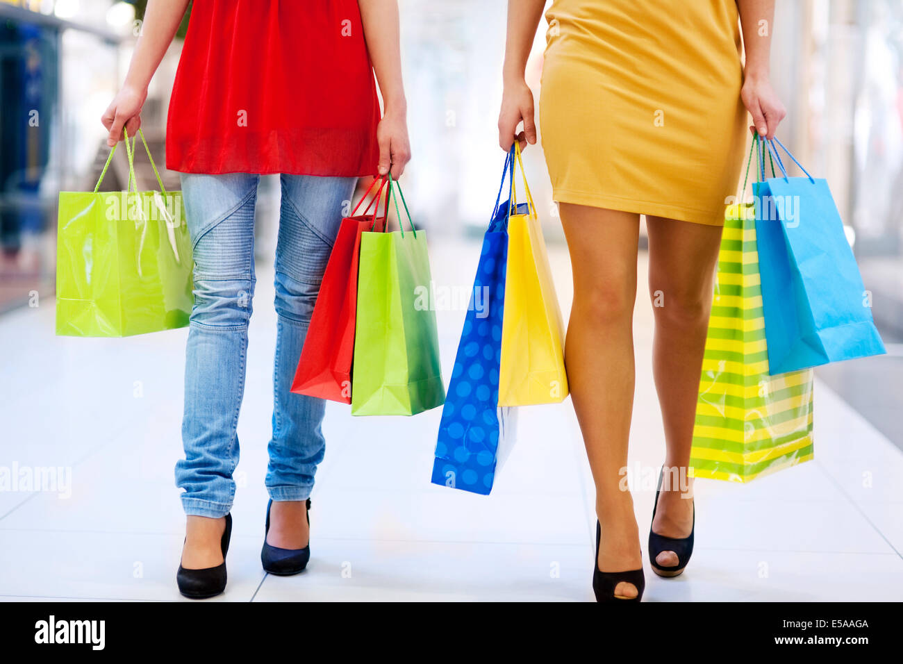 Low angle view of young friends carrying shopping bags. Debica, Poland - Stock Image