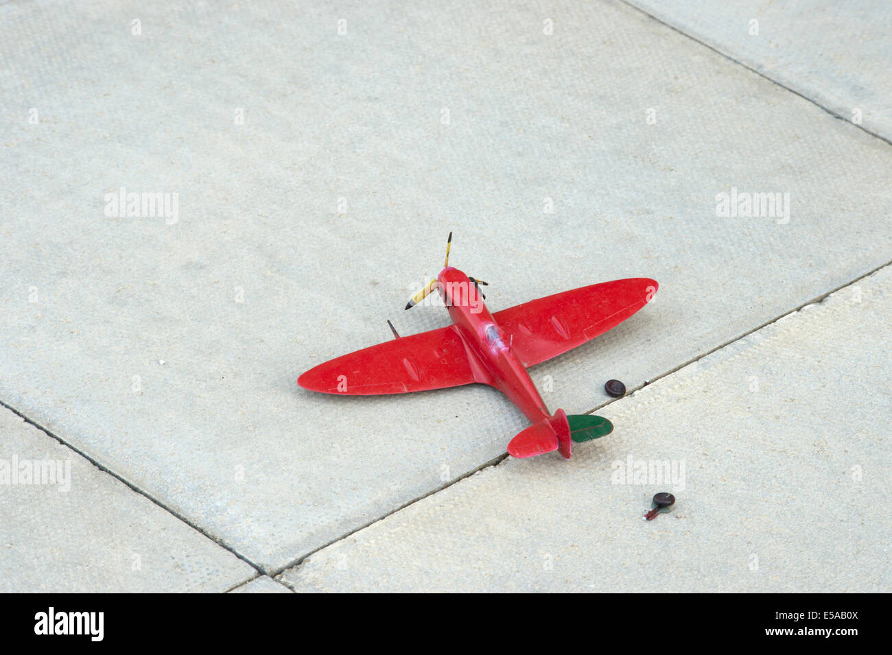 broken red toy spitfire aeroplane aircraft discard paving slab undercarriage ripped off - Stock Image