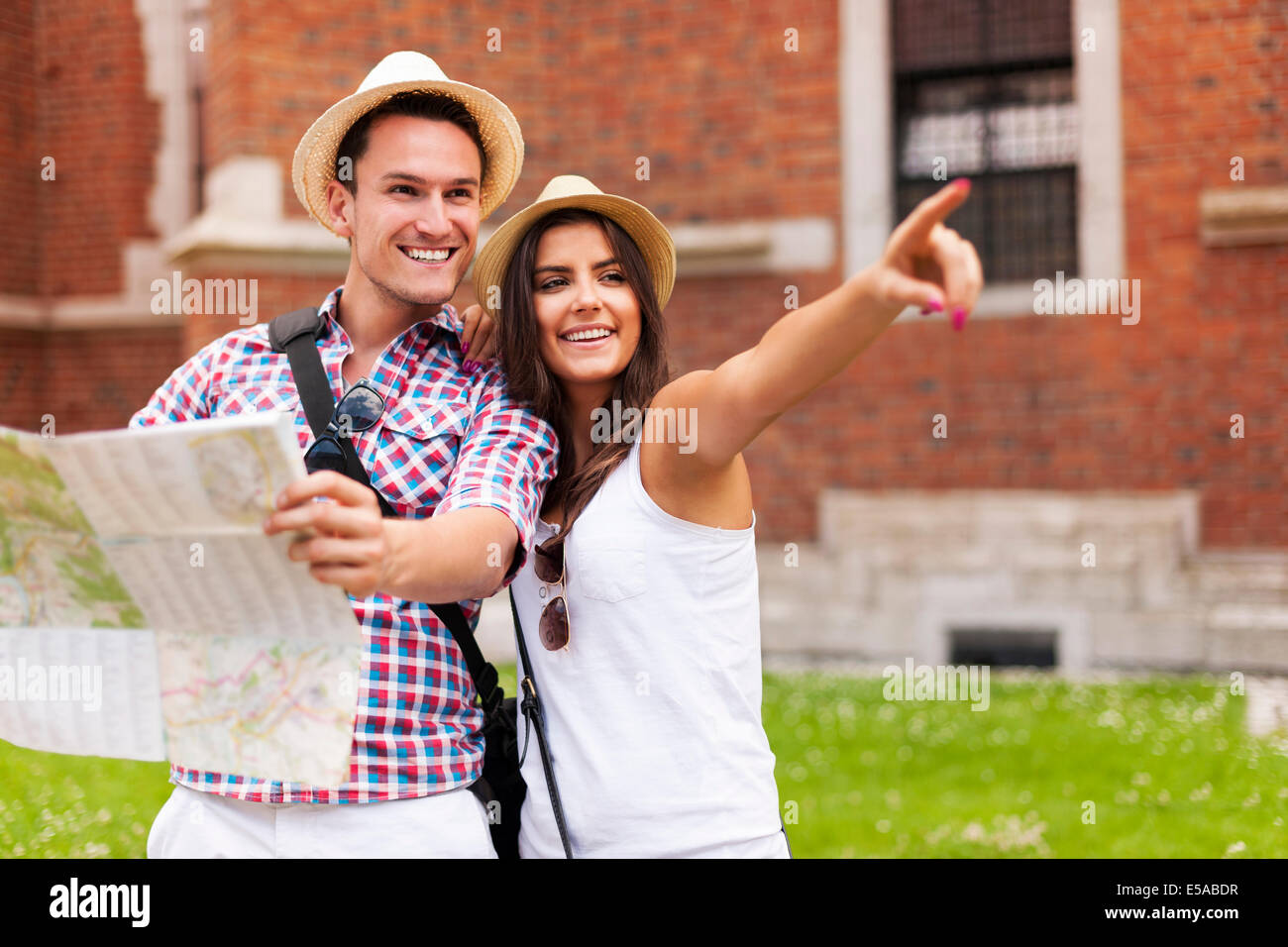 Woman pointing at something to her boyfriend during sightseeing, Debica, Poland - Stock Image