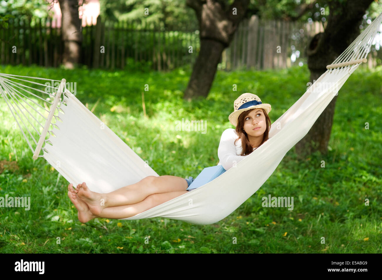 Young woman lying down on hammock, Debica, Poland. - Stock Image