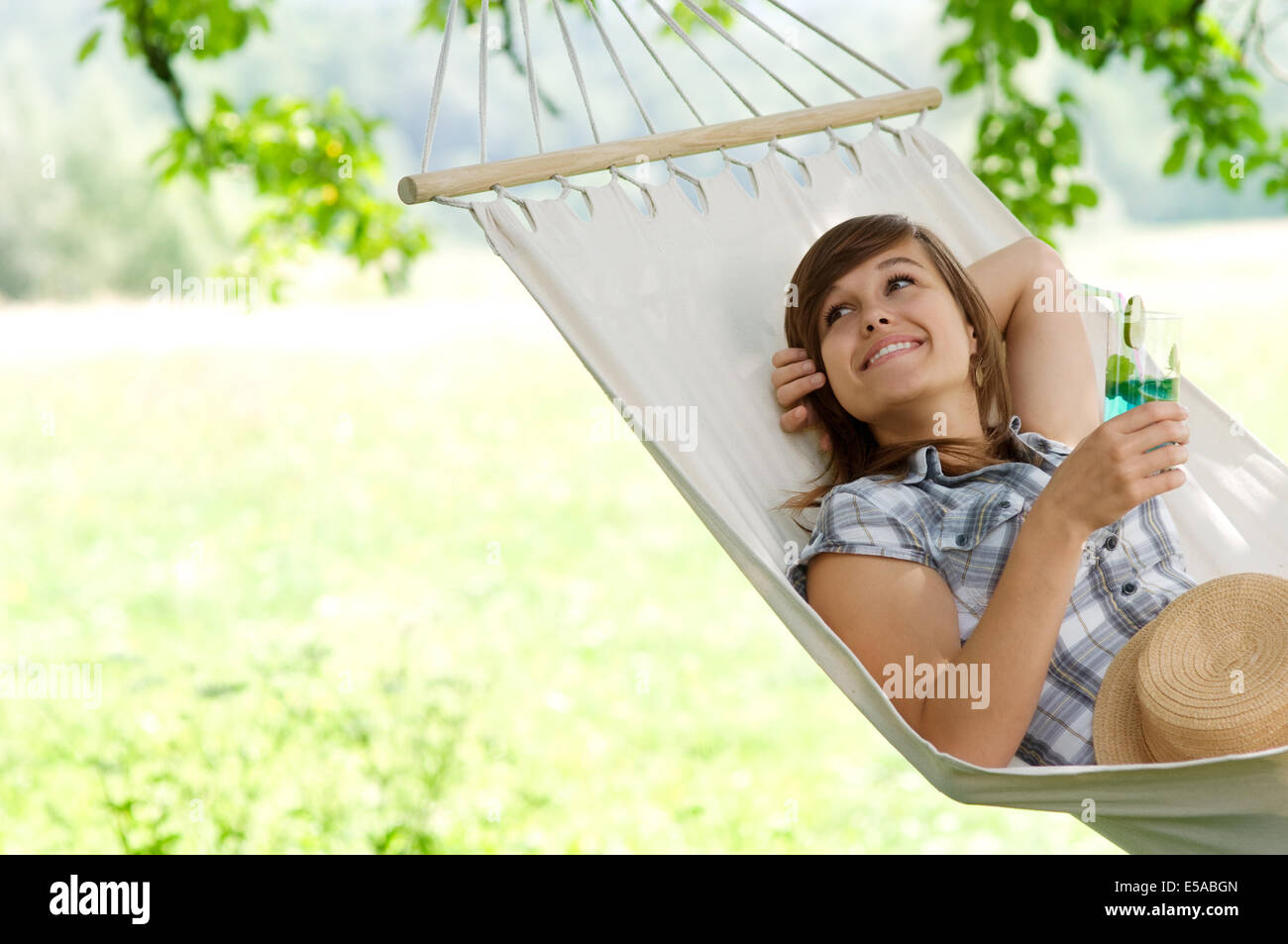 Young woman resting on hammock, Debica, Poland. - Stock Image
