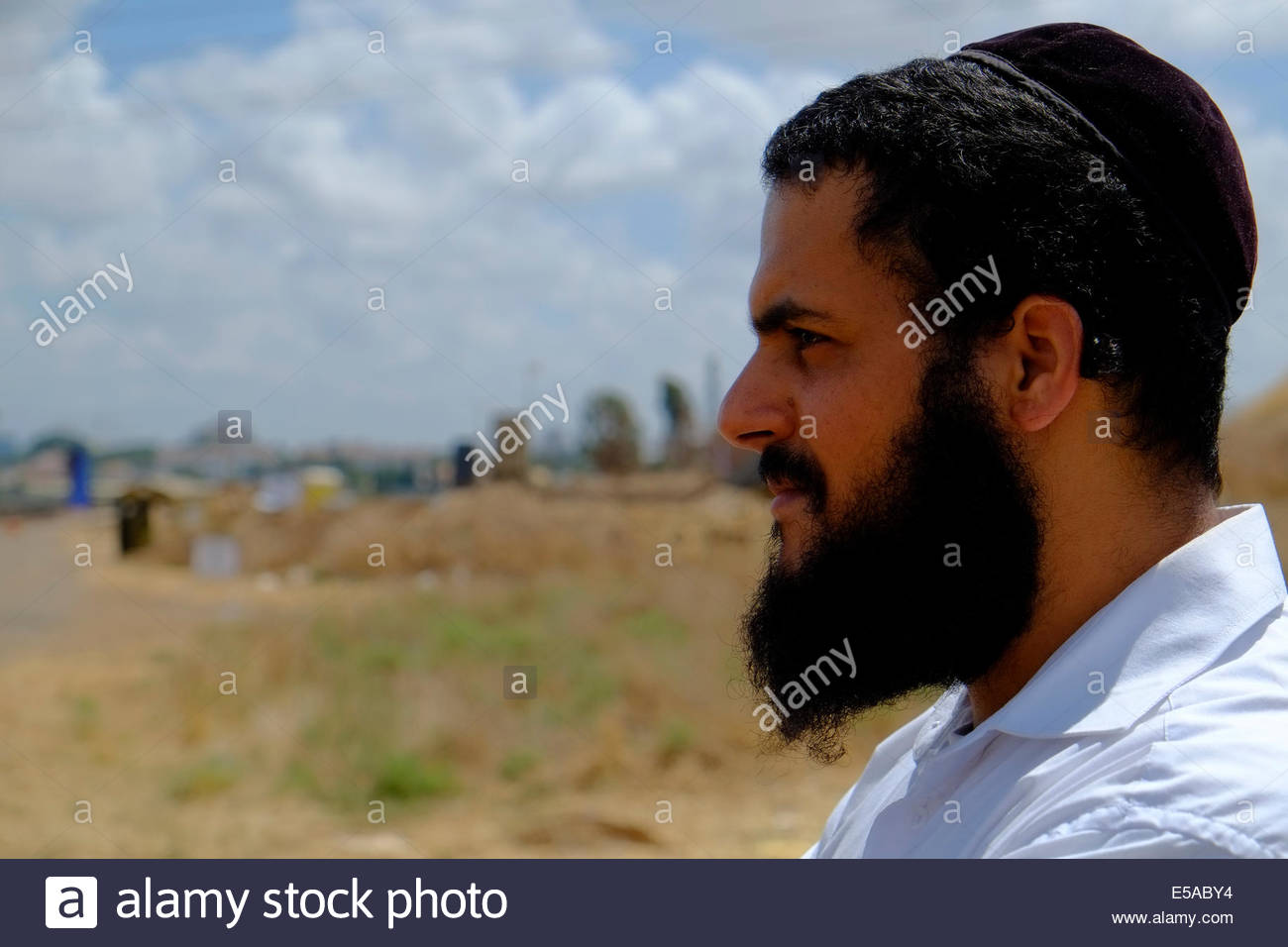 An ultra orthodox Jewish civilian with the Israeli anti missile device in background called The Iron Dome near Yahud - Stock Image
