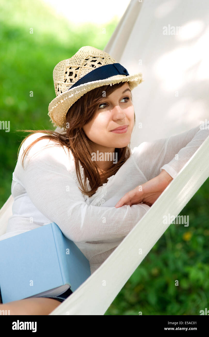 Young woman relaxing, in a hammock with book, Debica, Poland. - Stock Image