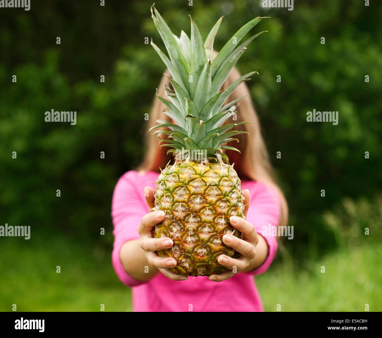 Young woman holding pineapple in her hands, Debica Poland - Stock Image