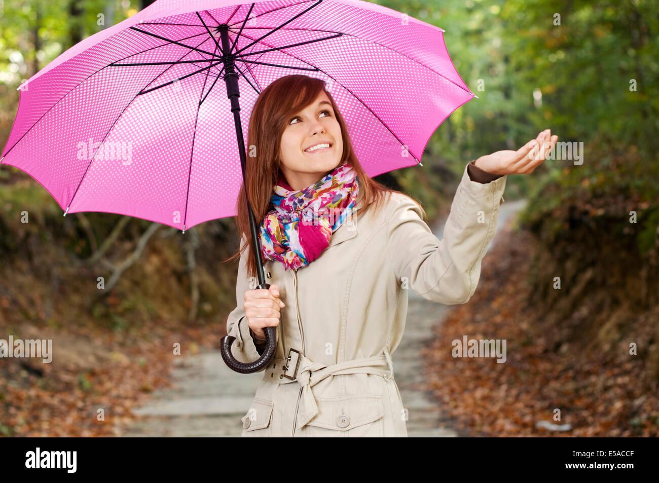 Beautiful girl with umbrella checking for rain, Debica ...