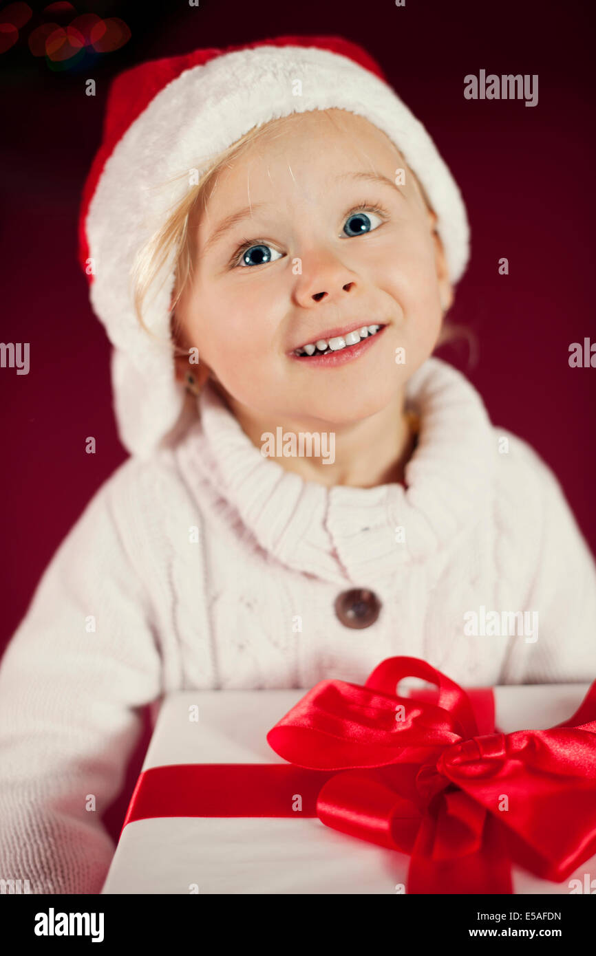 Cute girl with Santa hat holding Christmas gift, Debica, Poland - Stock Image