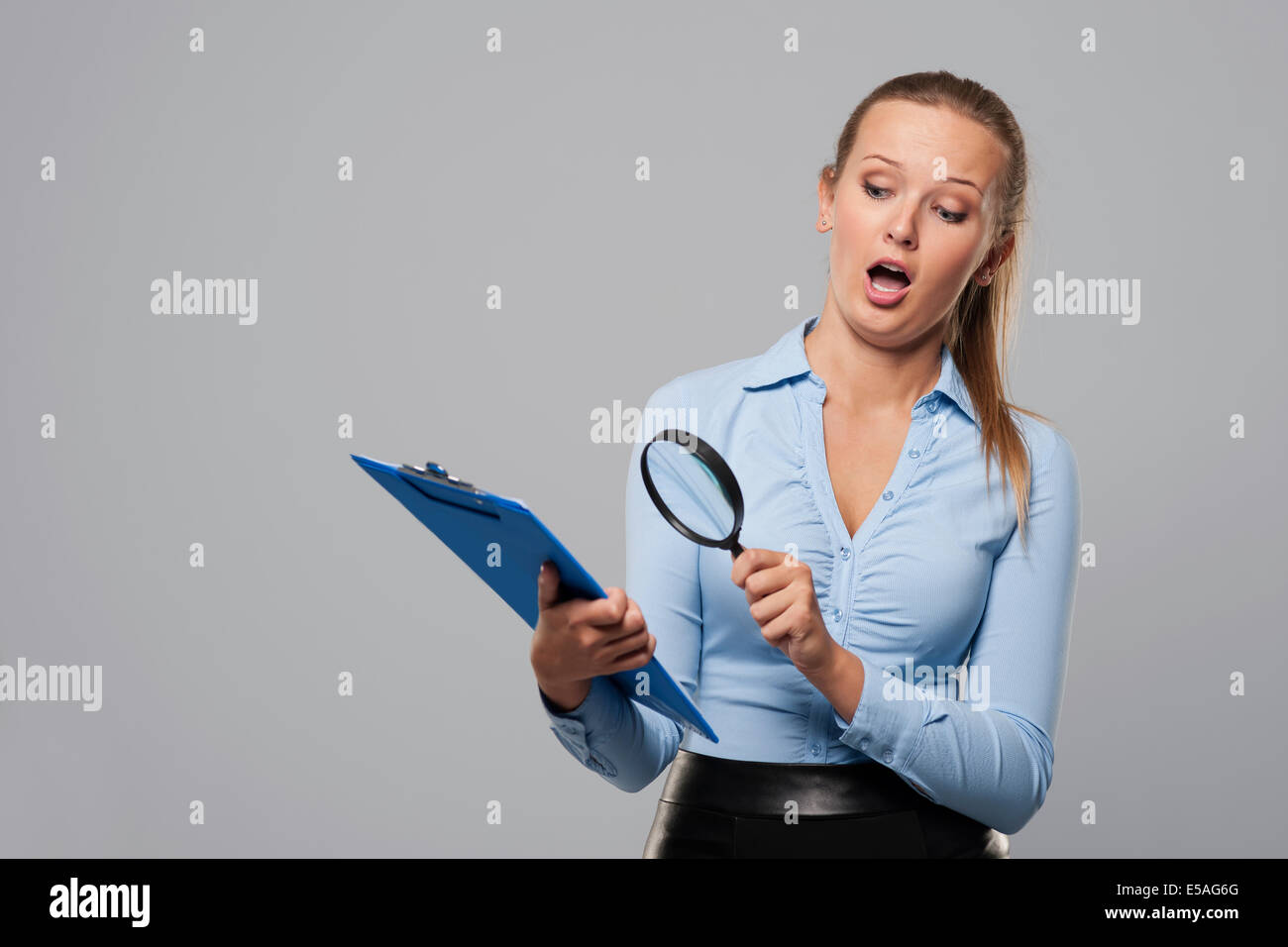Shocked woman looking at office documents with magnifier, Debica, Poland - Stock Image
