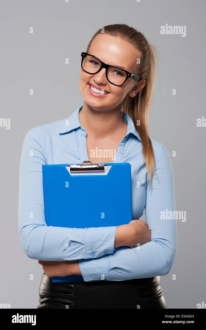 Happy businesswoman holding blue clipboard, Debica, Poland - Stock Image