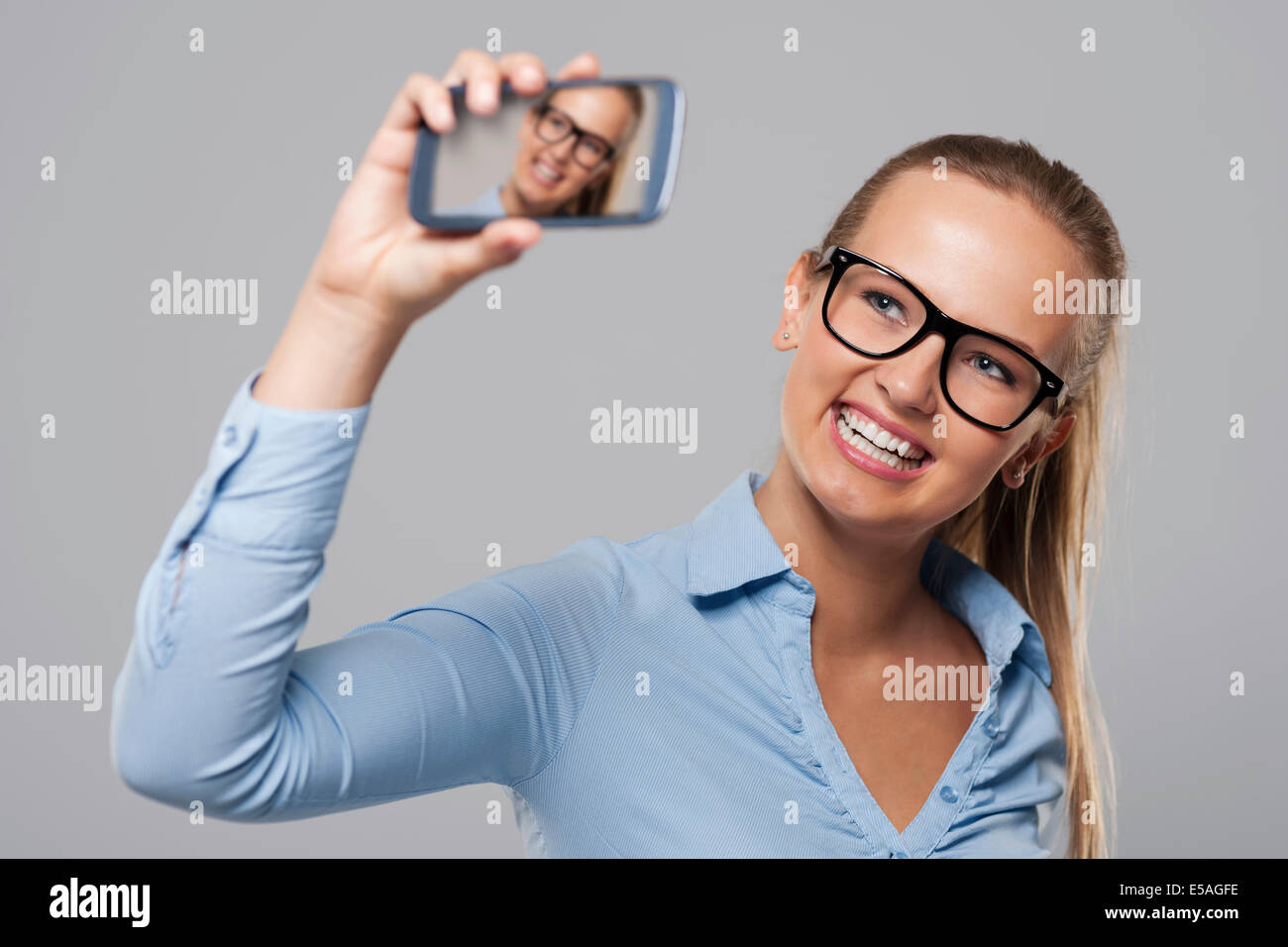 Blonde businesswoman wearing glasses taking self portrait photo, Debica, Poland - Stock Image