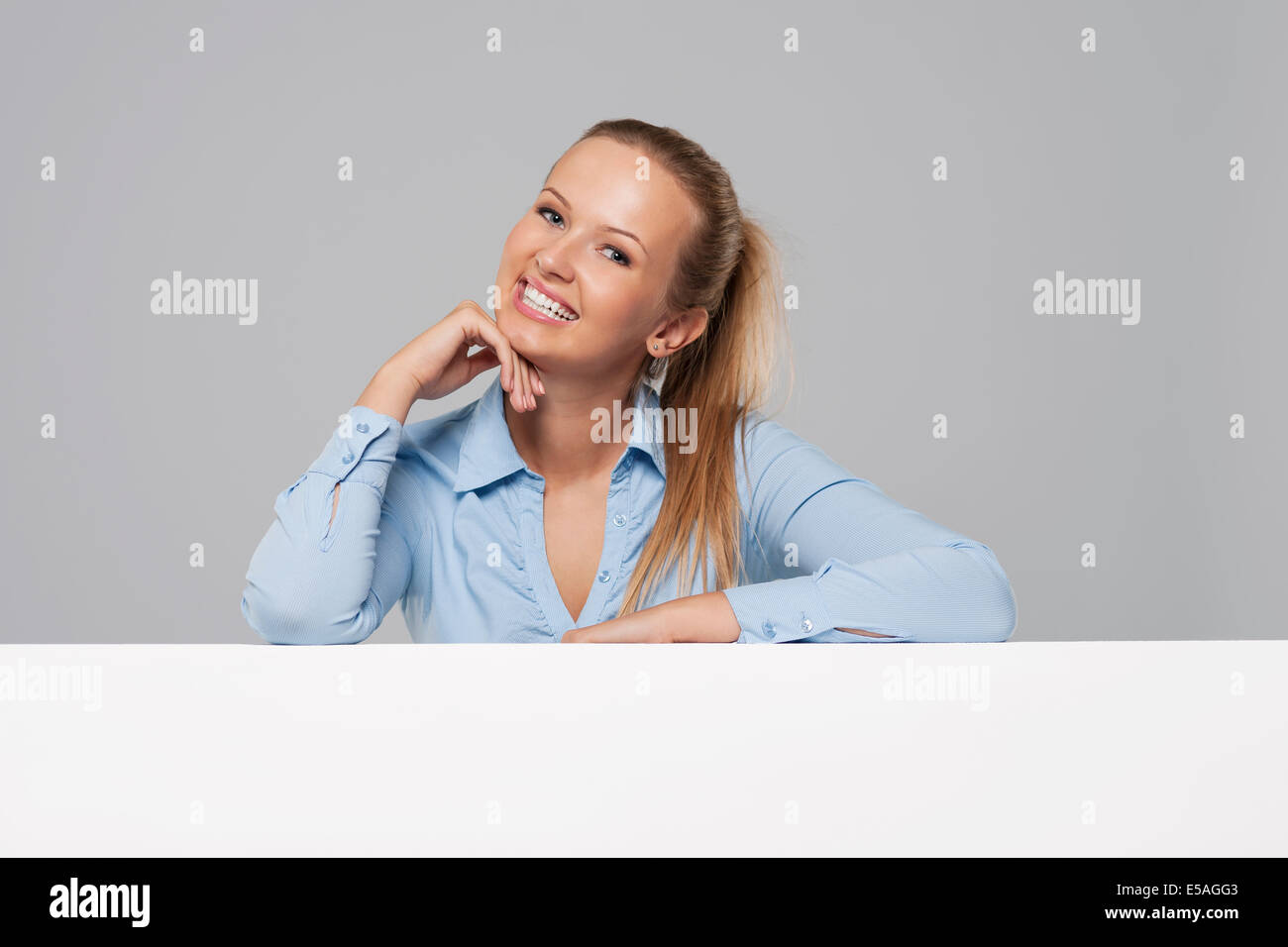 Businesswoman leaning at blank placard, Debica, Poland - Stock Image