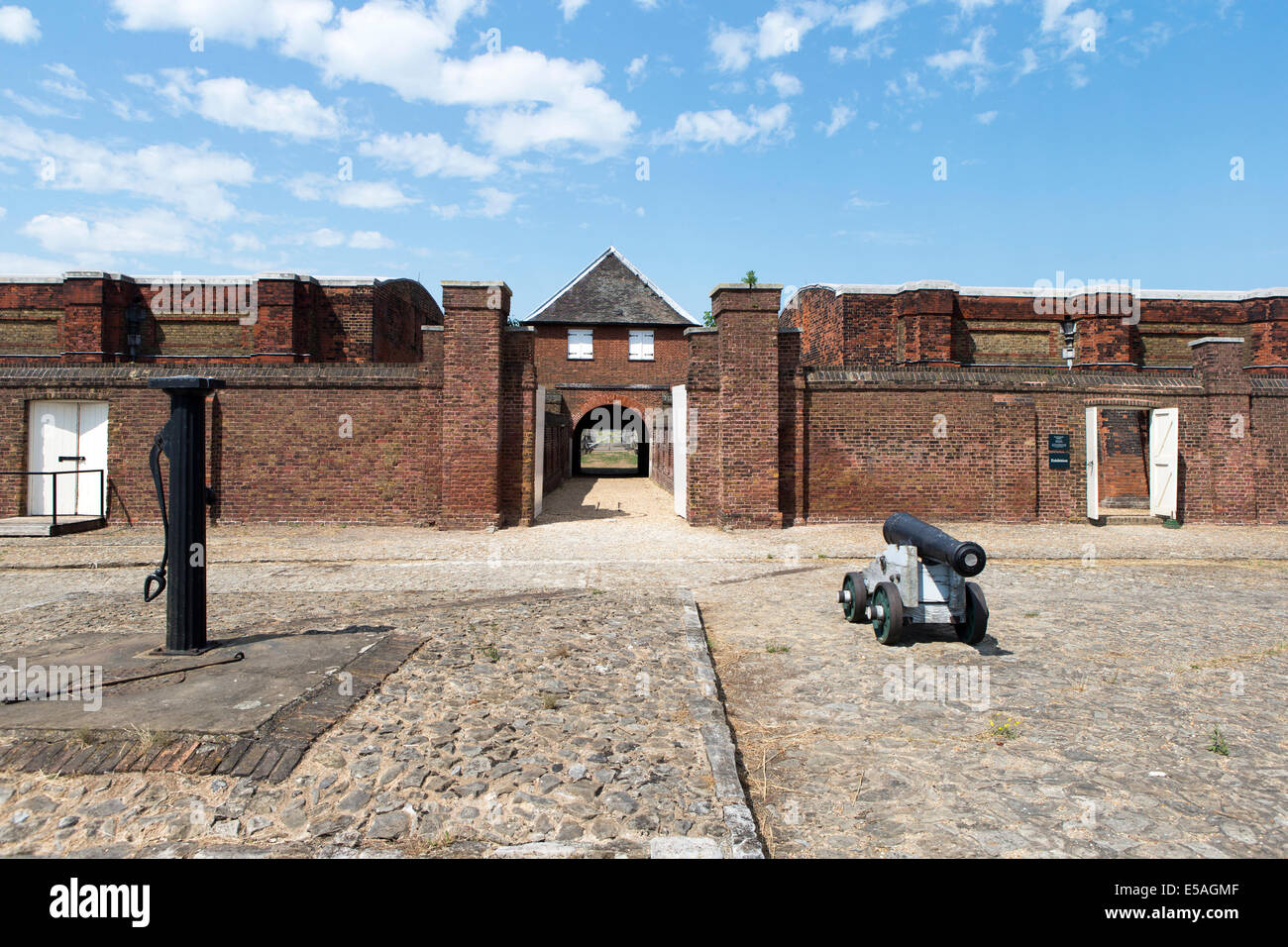 Cannon & Water pump on the parade ground in front of the Landport gate at Tilbury Fort, Essex, England, UK. - Stock Image