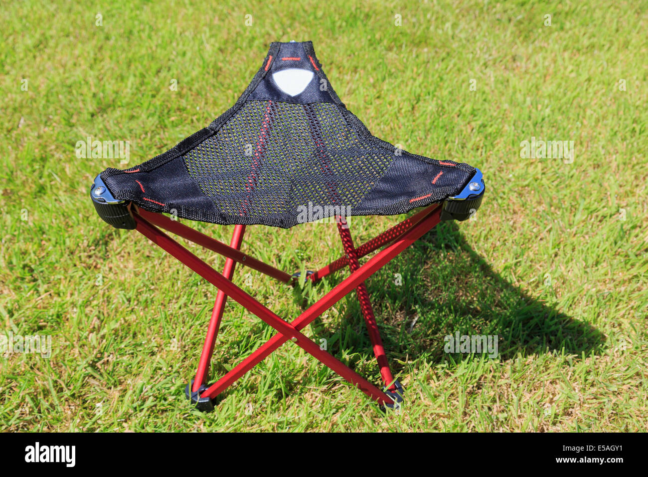 Folding portable three-legged tripod camping stool with a triangular mesh seat on grass in sunshine - Stock Image